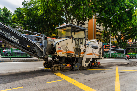 Singapore - May 27, 2017: Bitumen and Asphalt Paver Machine on a section of the road Editorial