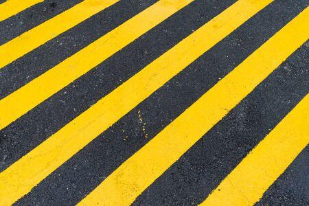 hazard stripes: Asphalt Background with diagonal black and yellow warning stripes, asphalt and yellow hazard lines Stock Photo