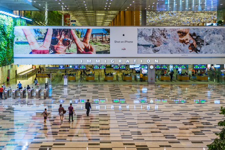 Singapore - July 16, 2017: Visitors walk around Arrival Hall Immigration area in Changi Airport. It has 4 passenger terminals, and is one of the largest transportation hubs in Asia