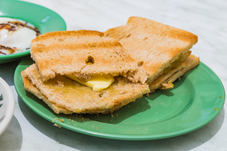 kopitiam: Traditional Singapore Breakfast called Kaya Toast, Bread with Coconut Jam and Half-boiled eggs, Selective Focus Stock Photo