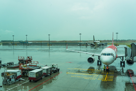 Singapore - August 12, 2017: Changi Airport Jetway for boarding passengers attached to the airplane in the raining day, an airplane stationary at airport passengers boarding to the plane Editorial