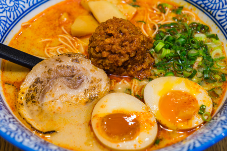 Japanese Tamago spicy Ramen with Cha Shu pork, Menma bamboo shoot and Ajitsuke Tamago boiled egg in a bowl on wooden background Stock Photo