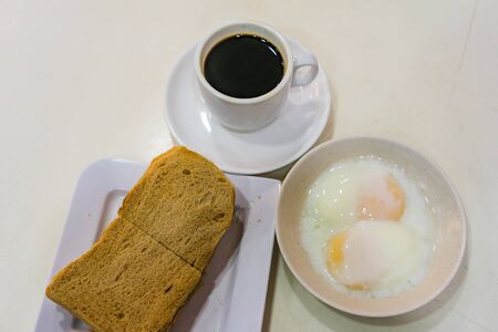 Singapore Breakfast called Kaya Toast, Coffee bread and Half-boiled eggs, Chinese coffee in vintage mug and bread toast with a local jam made from eggs, sugar and coconut milk, The fractal on the cup is generic print