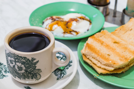 kopitiam: Singapore Breakfast called Kaya Toast, Coffee bread and Half-boiled eggs, Chinese coffee in vintage mug and bread toast with a local jam made from eggs, sugar and coconut milk, The fractal on the cup is generic print