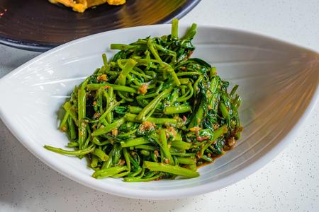 중국 튀긴 물 시금치 매운 칠리 마늘와 싱가포르에서 하얀 접시에 간장 Sambal Kangkong