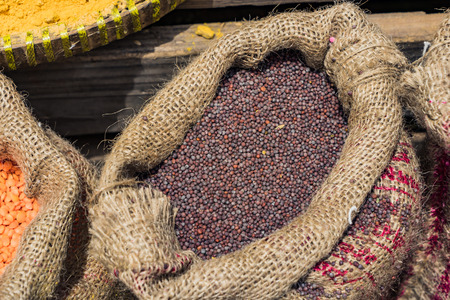 Sack of dried berries coffee beans on the wooden table background at market