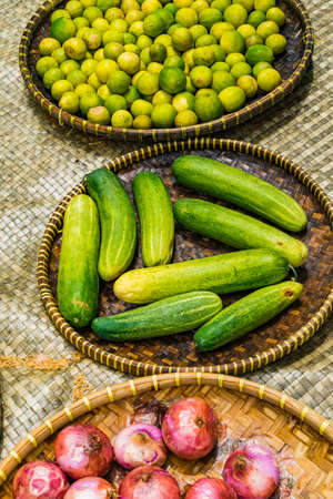 Fresh cucumbers and lemon lime in the tray on the wooden table background at the market