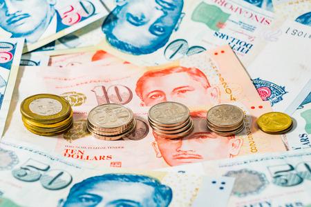 Pièces de monnaie et billets de dollar de Singapour sur fond blanc, le dollar de Singapour est la monnaie officielle de Singapour