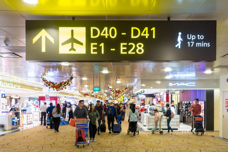 Singapore - January 6, 2018: Visitors walk around Departure Hall in Changi Airport. It has 3 passenger terminals, one of the largest transportation hubs in Asia and serves more than 100 airlines Publikacyjne