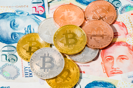 Bitcoin Cryptocurrency coins on top of Singapore Dollar banknotes on White background, The Singapore dollar is the official currency of Singapore, Concept crypto currency over the current currency