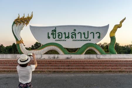 Kalasin, Thailand - December 23, 2017: Tourist girl take a photo of landmark spot at Lam Pao Dam in Kalasin province, Thailand.