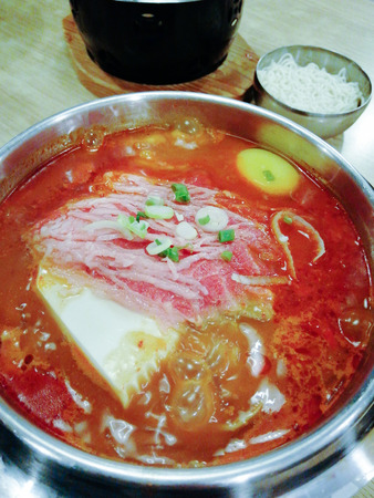 Delicious Korean food Yukgaejang spicy beef soup, Yukgaejang Hot pot is Korean stew made with kimchi, noodles, cheese, ham, sausage, mussels, prawn and vegetables