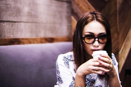 Asian women drinking coffe in the cafe