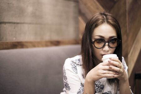 Asian woman  drinking coffee in a cafe