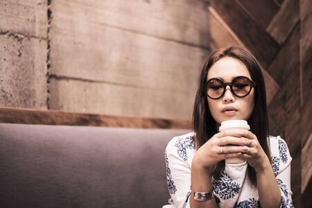 Asian woman  drinking coffee with feeling thinking in a cafe