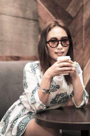 Asian woman drinking coffee and smiling in the cafe