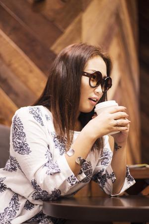 Asian woman  drinking coffee in a cafe happy feeling