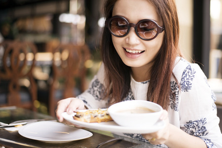 Happy young women eating mushroom cream soup and oyster cheese bread Stock Photo