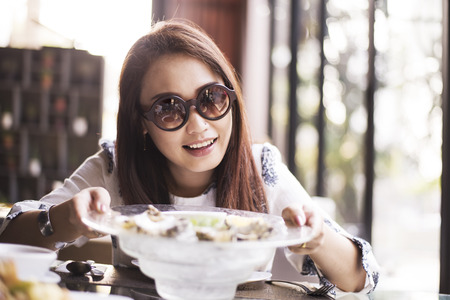 Happy young women eating Raw oysters  filtered warm tone Stock Photo