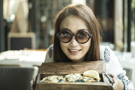 Happy young women eating baked oyster with cheese