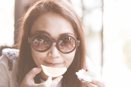 Potrait lovely Asian women eating shellfish raw oyster filtered warmtone picture at resturant