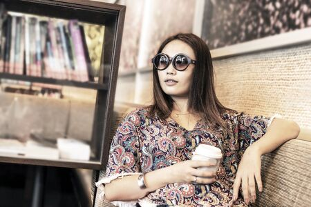 Asian woman drinking coffee and relaxing in the cafe