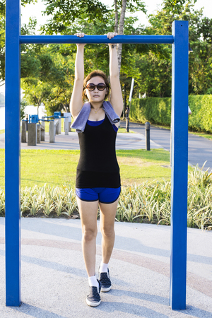 Asian woman doing exercises at the park outdoor on  a vertical bars Stock Photo