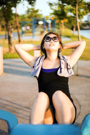 Exercise Asian girl doing situps  at the park out door Stock Photo