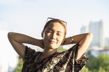 Asian girl feeling happy when sunset