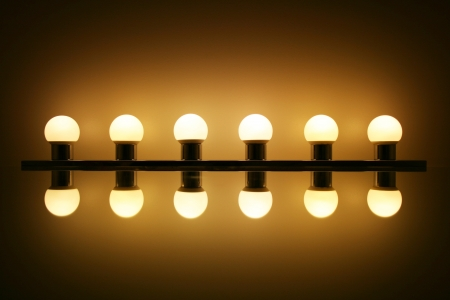 Six light bulbs with reflection on a mirror
