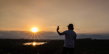 man standing and take picture with phone in sunset background