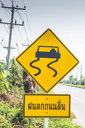 A sign showing the slippery car on the road (Thai word is mean bewear raining slippery road) Standard-Bild