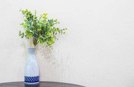 plastic leaf in jug on white wall background Standard-Bild