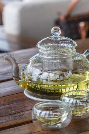 Chamomile tea in  glass kettle on wood table Standard-Bild