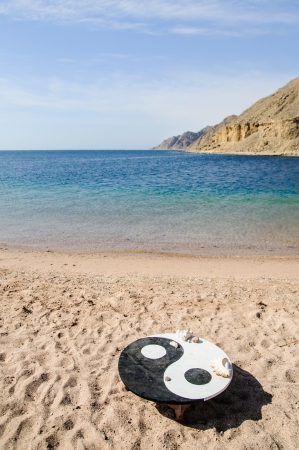 landscape wit the symbol of Yin Yang on the beach photo