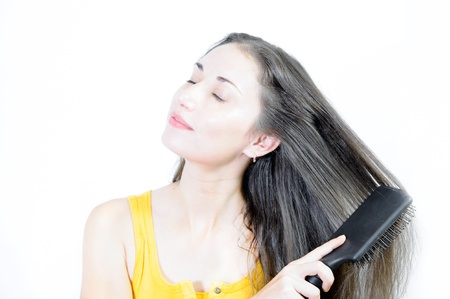 Young beautiful brown-haired woman is combing her hair photo