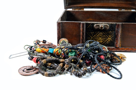 Heap of jewelry near wooden chest isolated on white background photo