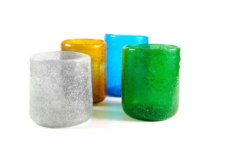 group of multi coloured glass cups on white background photo