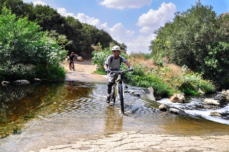 cyclist is crossing the river with a mountain bike