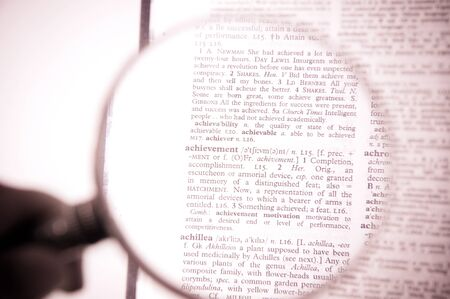 A magnifying glass on the word achievement on a dictionary photo