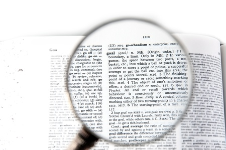 A magnifying glass on the word goal on a dictionary photo