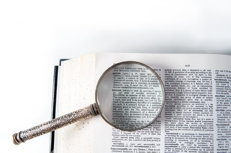 A magnifying glass on the word success on a dictionary