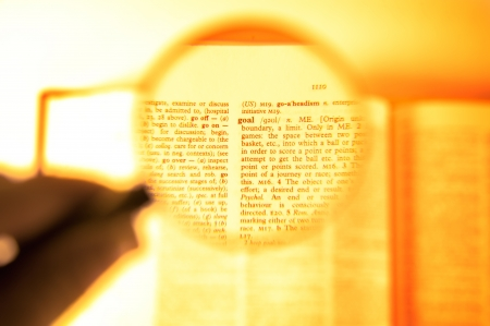 A magnifying glass on the word goal on a dictionary