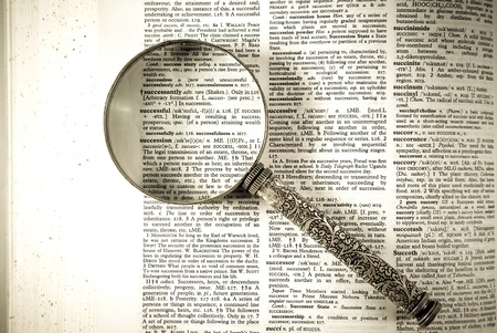 A magnifying glass on the word successful on a dictionary photo