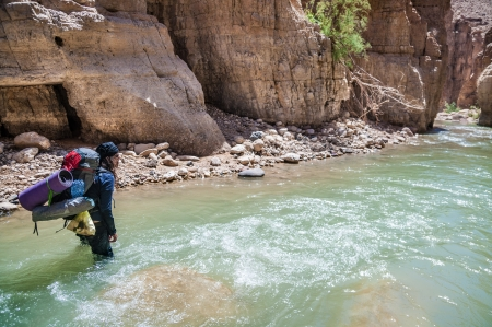 Man crossing the creek in Wadi Hasa in Jordan photo