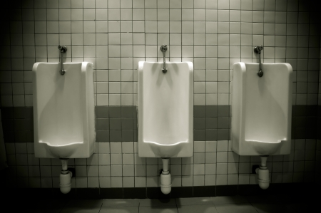 row of urinals in empty public restroom photo
