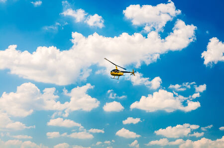 Yellow tourist Helicopter in the blue sky Stock Photo