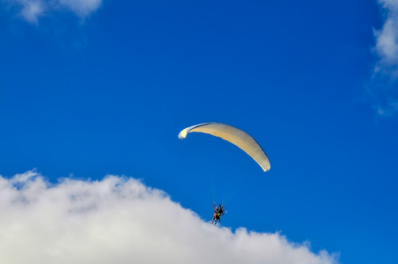 View on flying paragliding in the cloudy blue sky Stock Photo