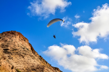 Flying paragliding near the cliffs on blue sky background
