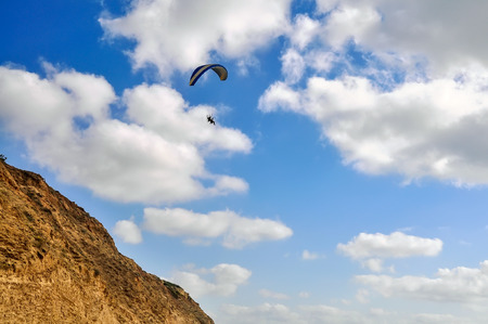 Flying paragliding near the cliffs on cloudy sky background